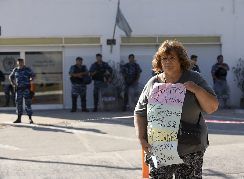 Una mujer aguardó la llegada de los imputados. Varias personas expresaron su repudio para con el grupo de amigos que asesinó a patadas a Fernando Báez. (Télam)