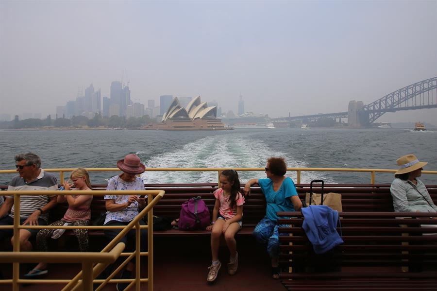 Lugareños son evacuados con el palacio de la Ópera de Sidney entre brumas.