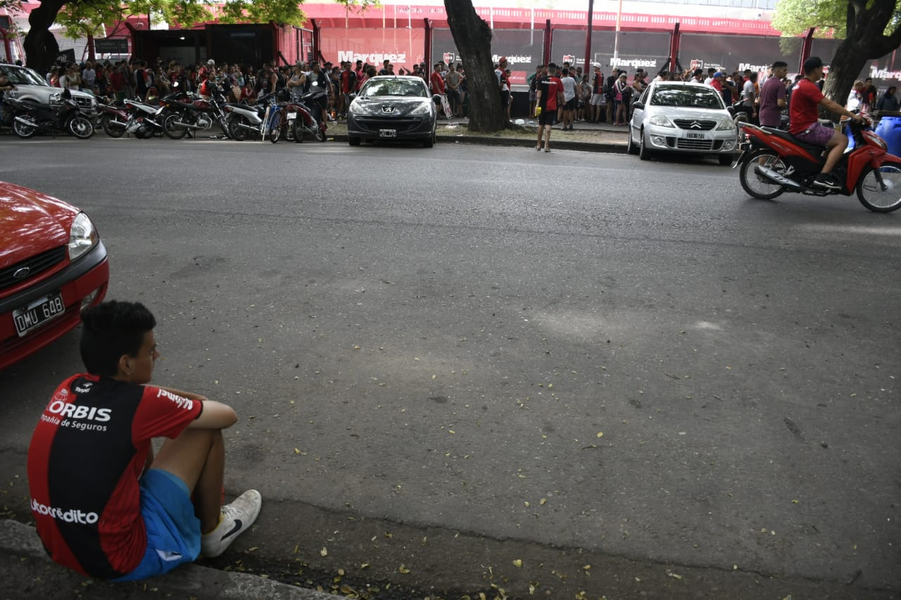 Un joven descansaba frente a la larga cola hacia la puerta 6 del Coloso.