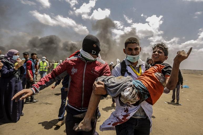 Un grupo de manifestantes palestinos carga con un herido durante unos enfrentamientos con los soldados israelíes en Jan Younis, territorios palestinos. Foto: MohammedTalatene.