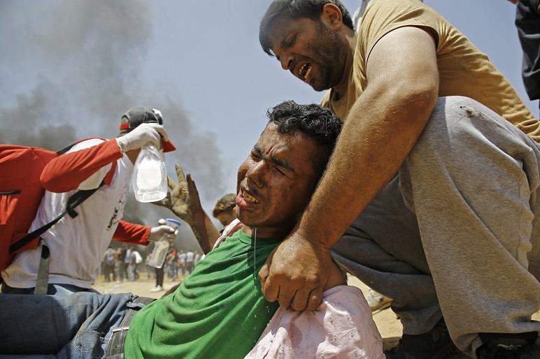 Paramédicos socorren a un palestino herido durante la represión del Ejército israelí.