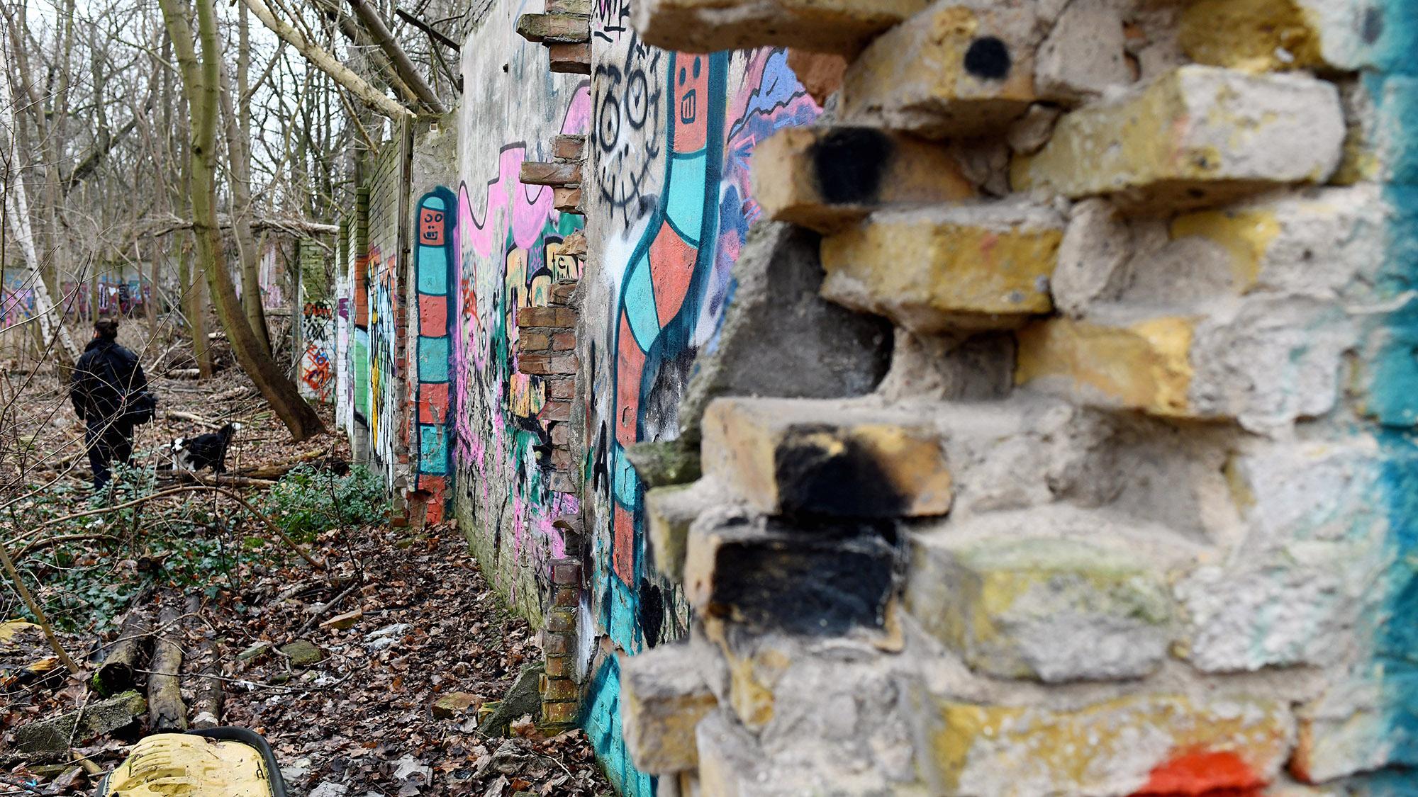 Una persona camina el 24/01/2018 junto a una parte del Muro de Berlín recientemente descubierta en el barrio de Pankow.