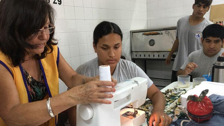 Los chicos de la escuela especial, felices con su nueva máquina de coser.
