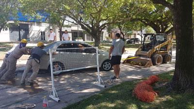 Los obreros ayudaron a sacar al auto del cemento fresco.