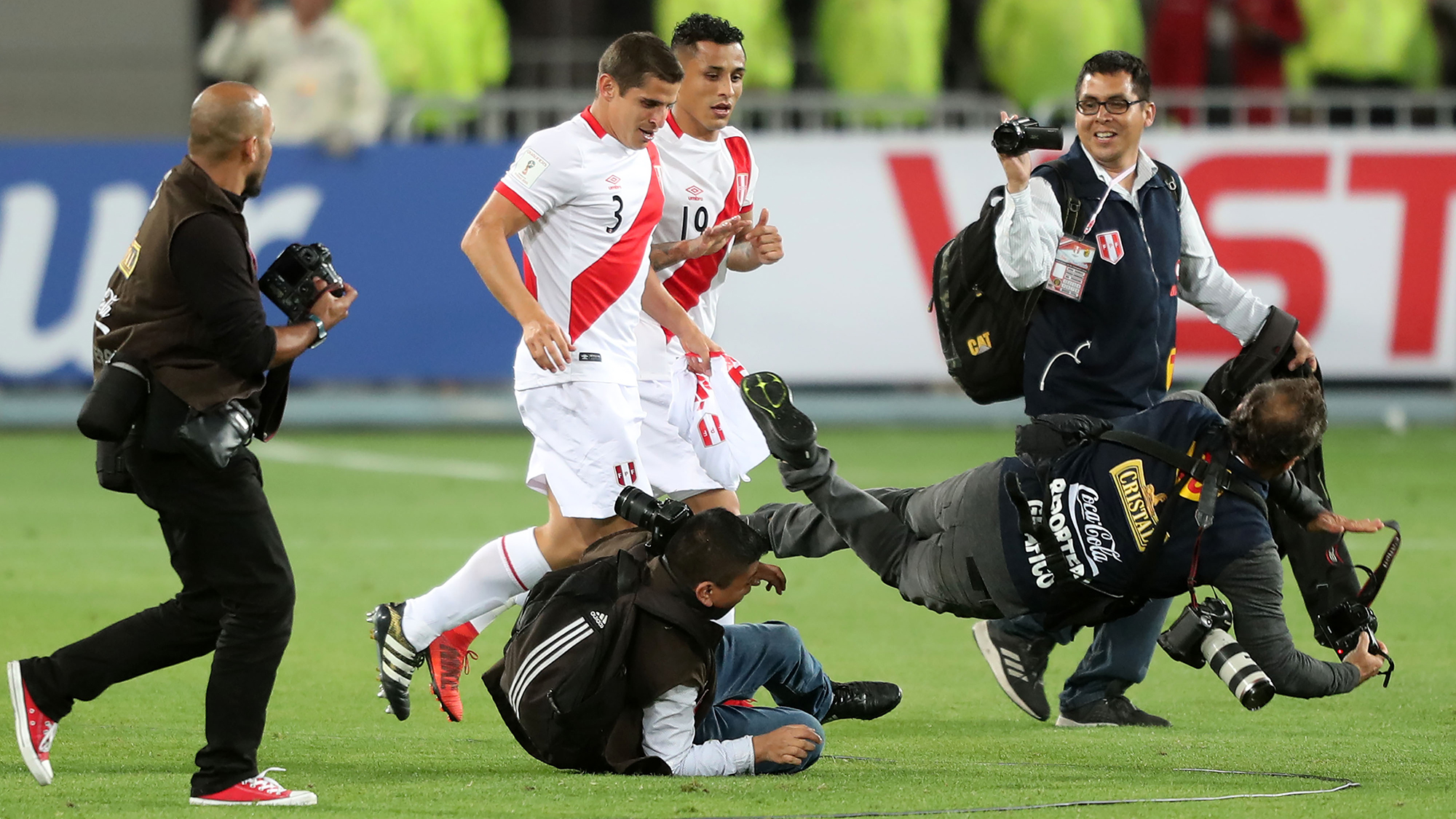 Dos reporteros gráficos caen mientras siguen la celebración de los peruanos Christian Cueva y Aldo Corzo.