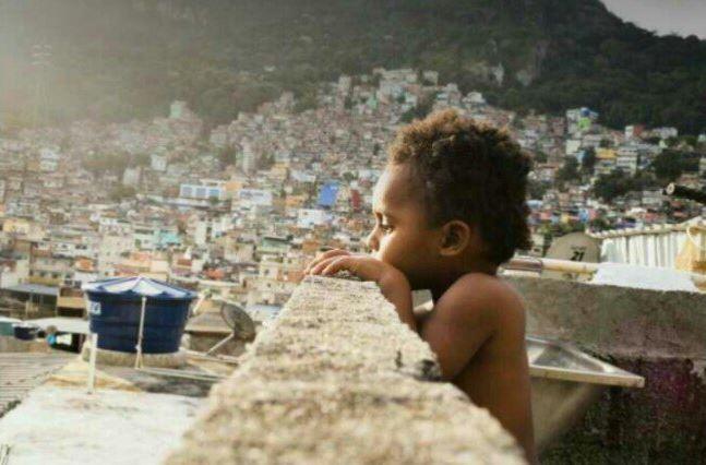 Un niño desde su hogar en la Rocinha, se asoma sobre la ladera del morro dondese extiende la populosa barriada. (@errejotacitou)