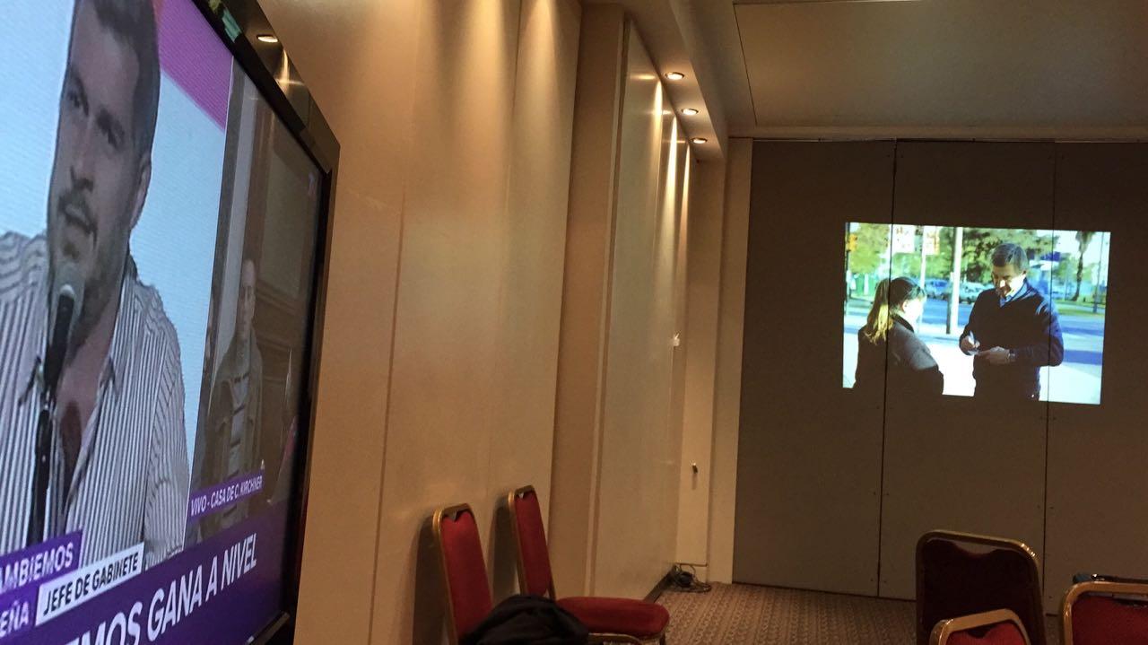 TN en una pantalla gigante en el bunker de Boasso, mientras las sillas esperan periodistas y militantes.