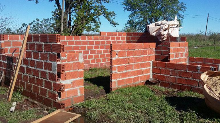 La familia está construyendo una vivienda de material muy cerca.