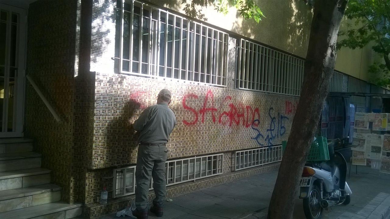 Un hombre intenta quitar las pintadas del frente de Cristo Rey. Foto: Rosario Plus