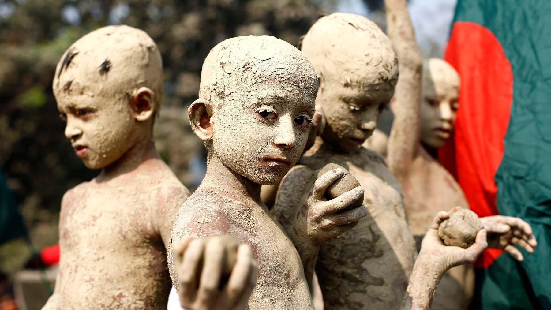 Niños cubiertos de barro asisten a un desfile con motivo del Día de la Victoria en Gazipur (Bangladesh)
