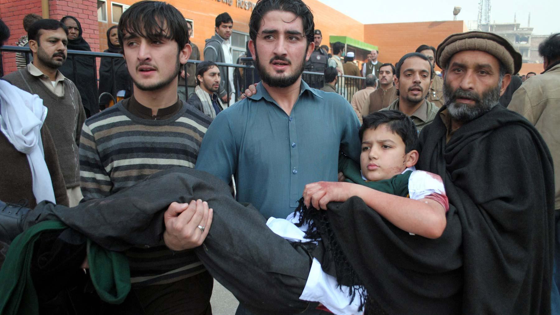 Personas trasladan a un niño lesionado a un hospital, en Peshawar, en el noroeste de Pakistán.