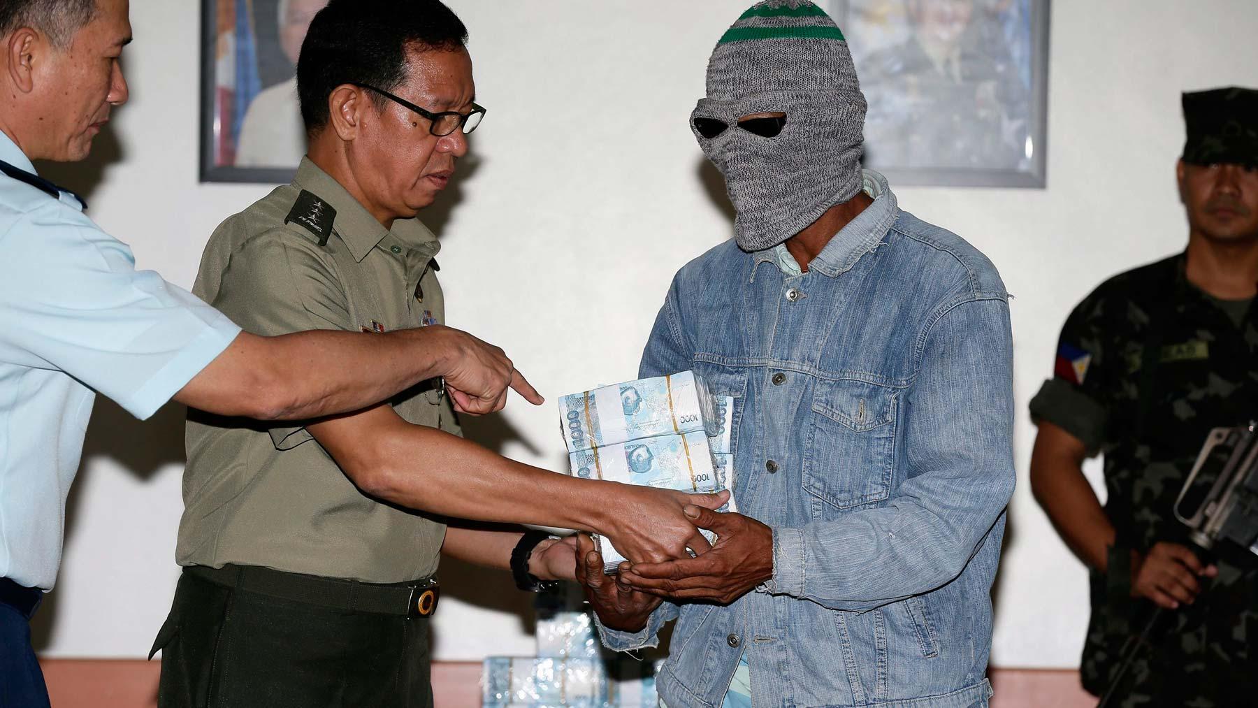 El general John Bonafos (2ºizda) entrega a un informante anónimo (2ºdcha) la recompensa de 5,3 millones de pesos filipinos (92.642 euros)