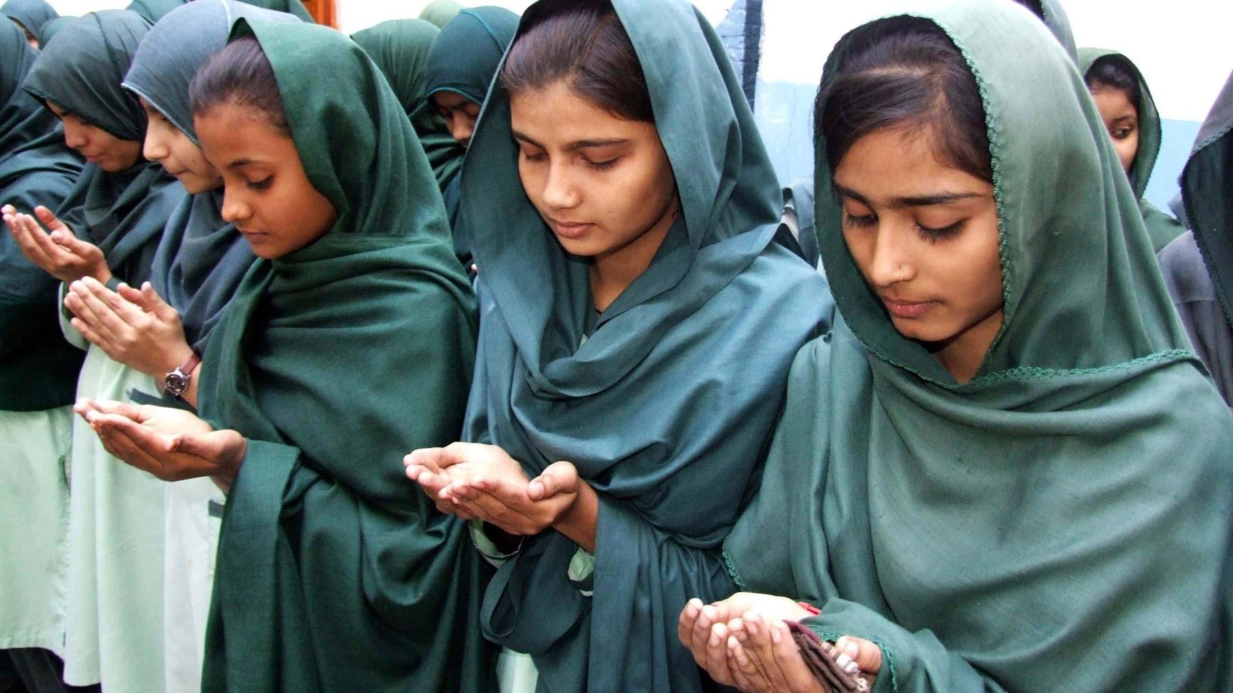 Varias alumnas rezan por los estudiantes asesinados alumnos en el ataque talibán contra un colegio gestionado por el Ejército en Peshawar