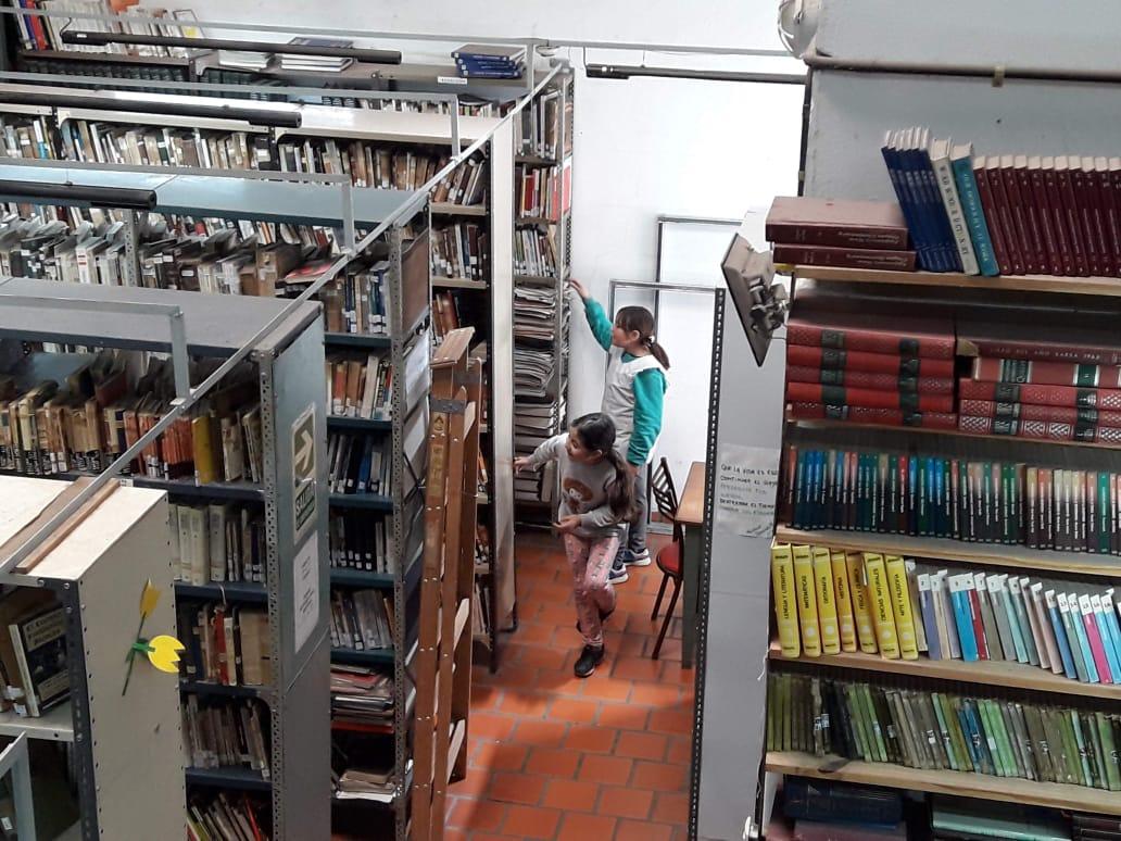 Niñas buscando libros en la biblioteca Alberdi, antes de la pandemia.