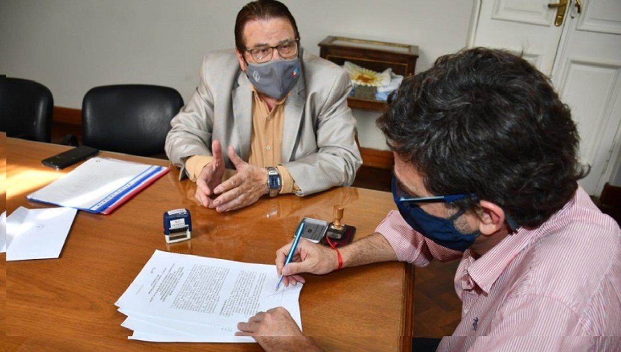 El Intendente Golosetti firma en presencia del senador departamental.
