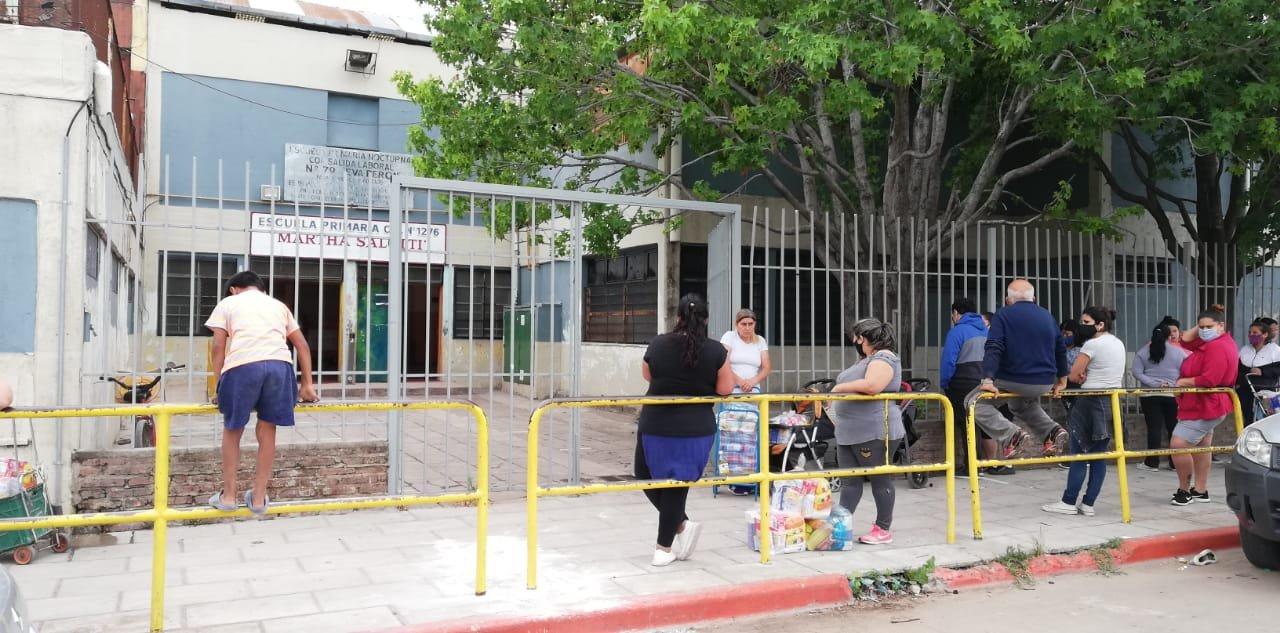 Padres aguardan en la vereda de una escuela de barrio por sus hijos. (foto Rosario Plus)